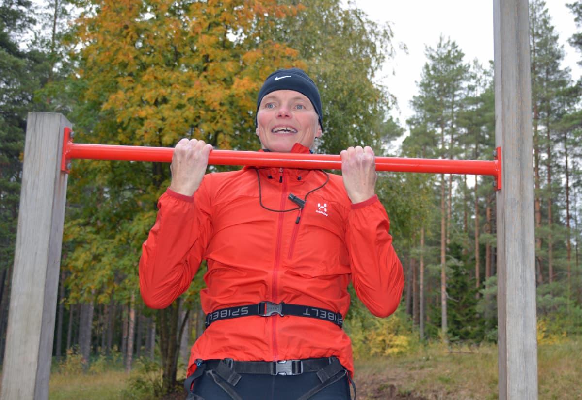 Teija Polso vetää leukoja metsässä olevassa telineessä.