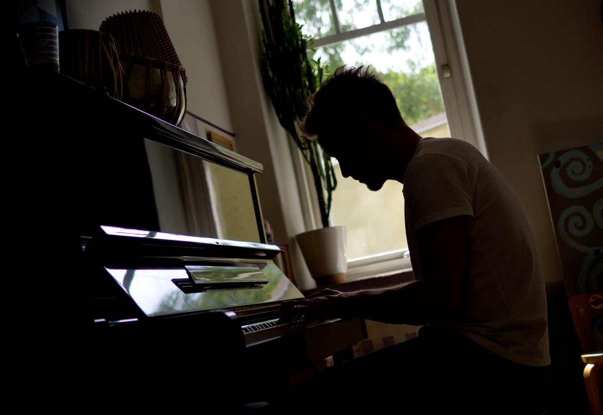 Reino Nordin kotonaan pianon ääressä.