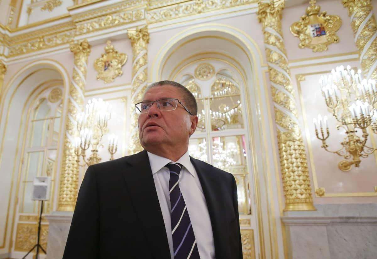 Uljukajev seisoo tummassa puvussa ylenpalttisen loisteliaalta näyttävässä salissa ja katsoo kuvassa vasempaan yläreunaan päin.