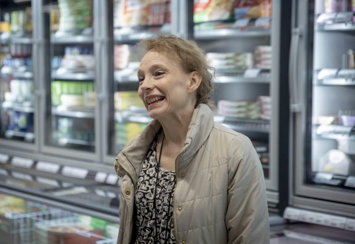 HOK-Elannon vastuullisuuspäällikkö Satu Kattilamäki seisoo S-Marketin pakastekaappien edessä ja nauraa.