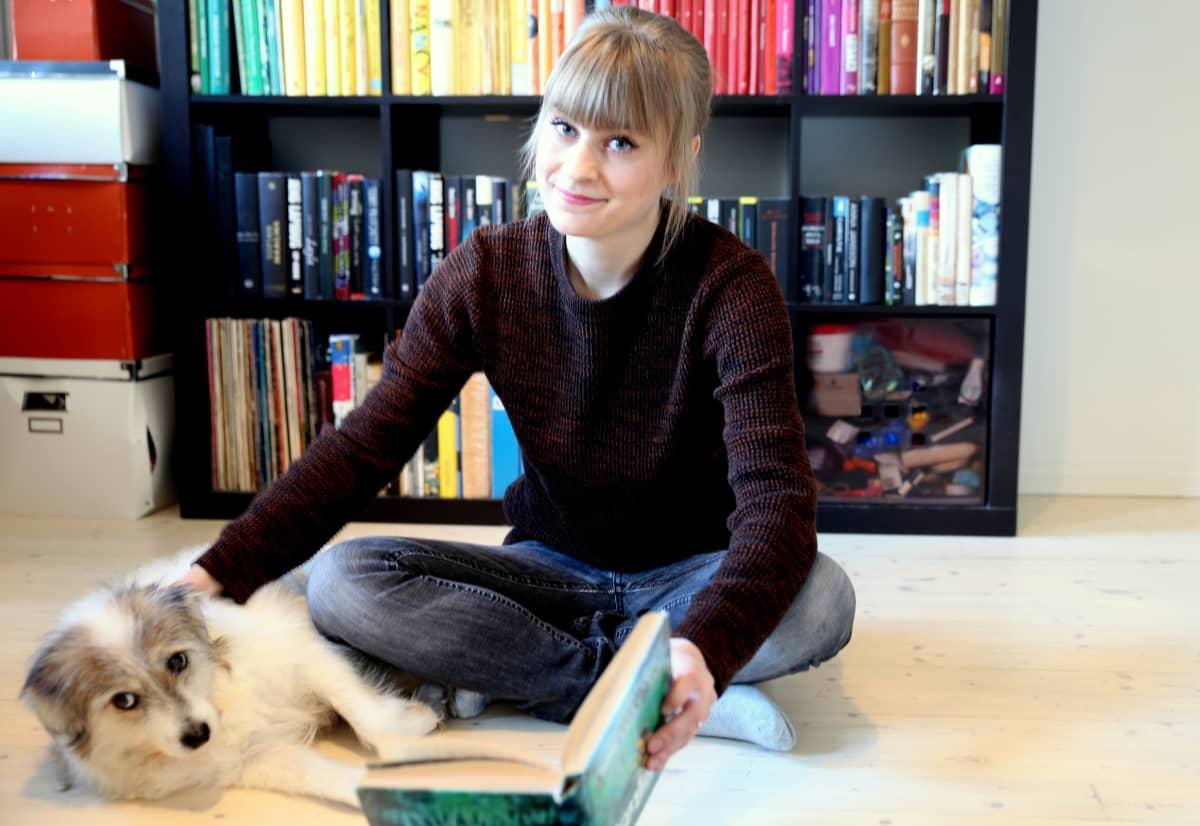 Nuori nainen istuu lattialla kirja kädessä ja koira vieressä. Taustalla on kirjahylly täynnä kirjoja.