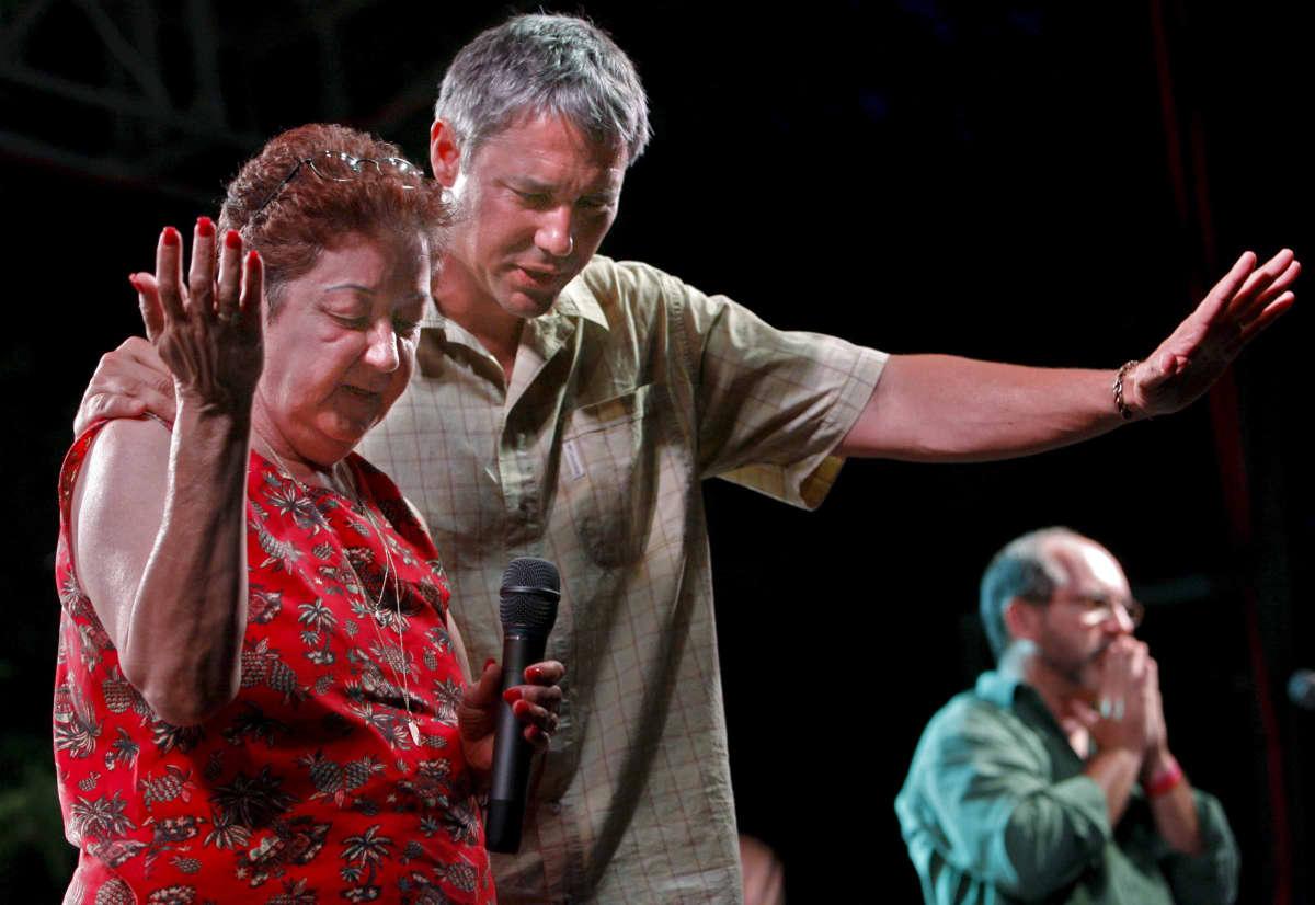 Nainen ja mies rukoilevat kädet ylös nostettuna. Pumamekkoisella naisella on mikrofoni kädessä.