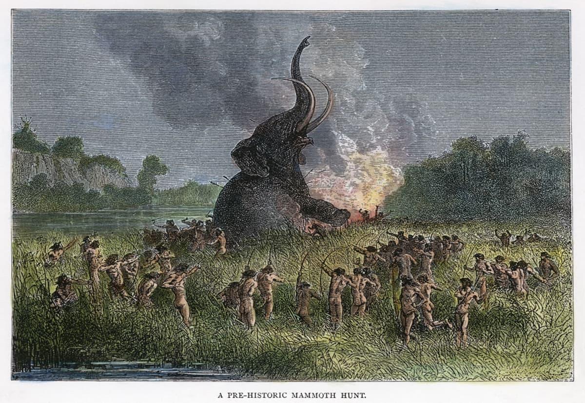 Kuvakaiverrus jousilla aseistautuneesta ihmisjoukosta piirittämässä maahan suistuvaa mammuttia.