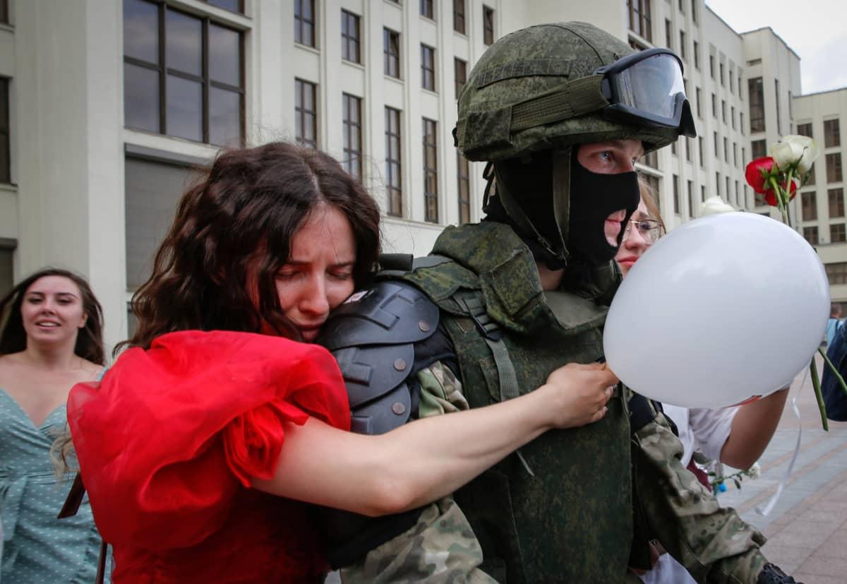 Mielenosoitukseen osallistunut nainen halasi sotilasta Minskin itsenäisyyden aukiolla perjantai-iltana.