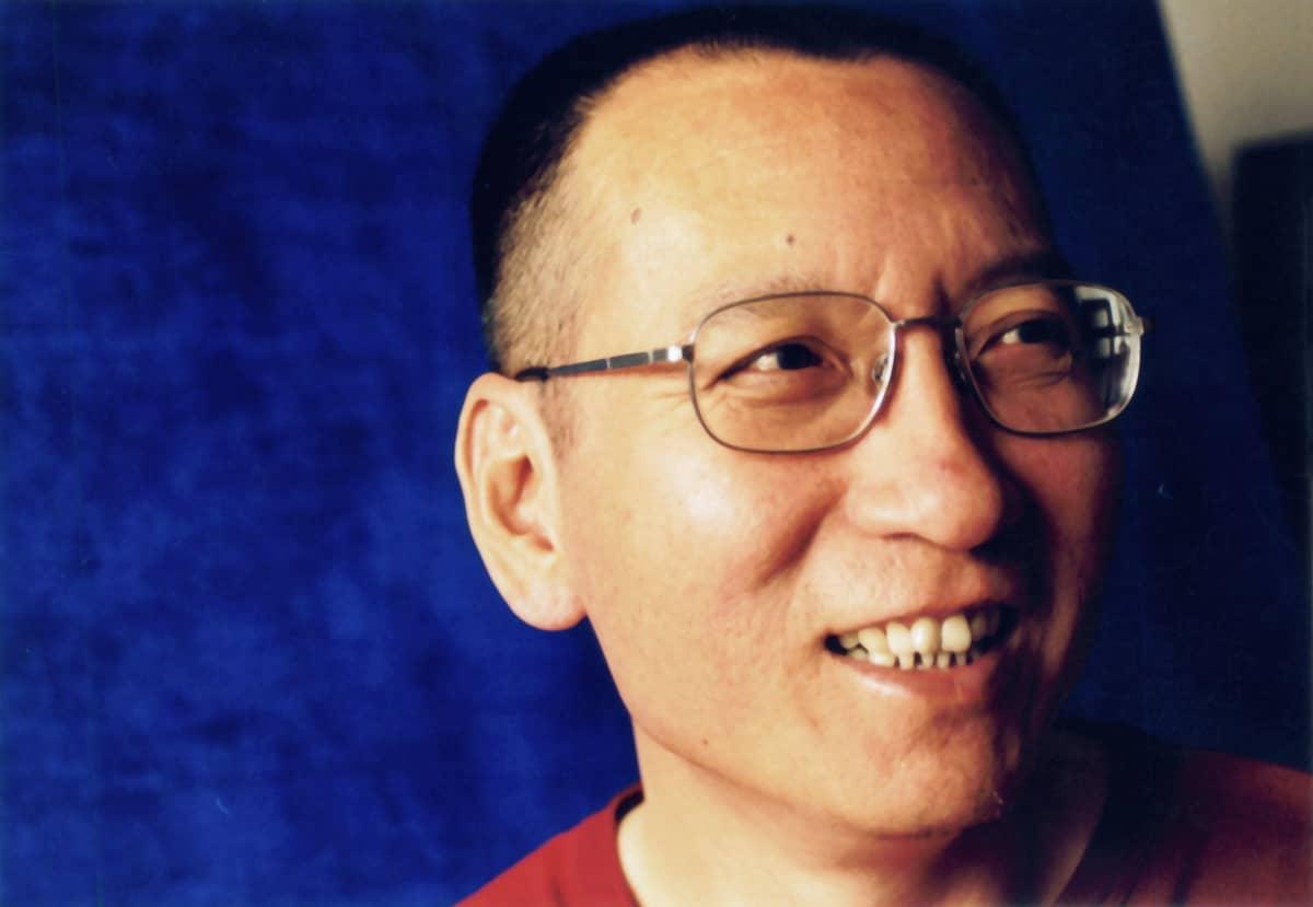 Liu Xiaobo hymyilee sinistä taustaa vasten.