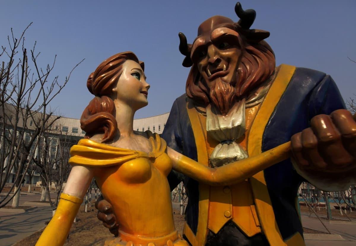 Kaunottaren ja hirviön animaatiohahmoihin perustuva patsas lehdettömien puiden ja suuren näyttelyrakennuksen edessä.