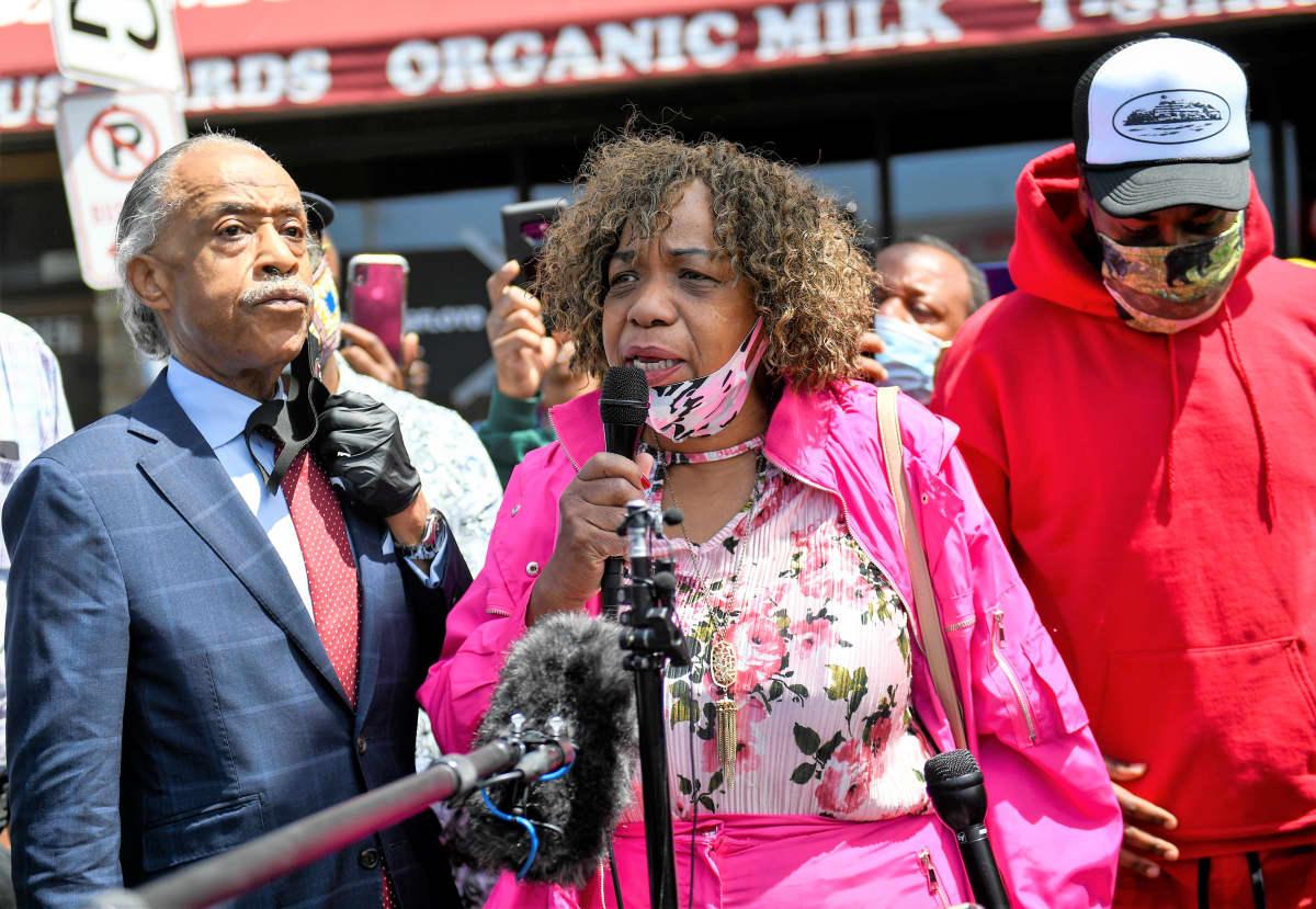 Eric Garnerin äiti Gwen Carr puhuu mikrofoniin. Al Sharpton kuuntelee vakavana vieressä. Taustalla näkyy väkijoukkoa ja elintarvikekaupan julkisivua.