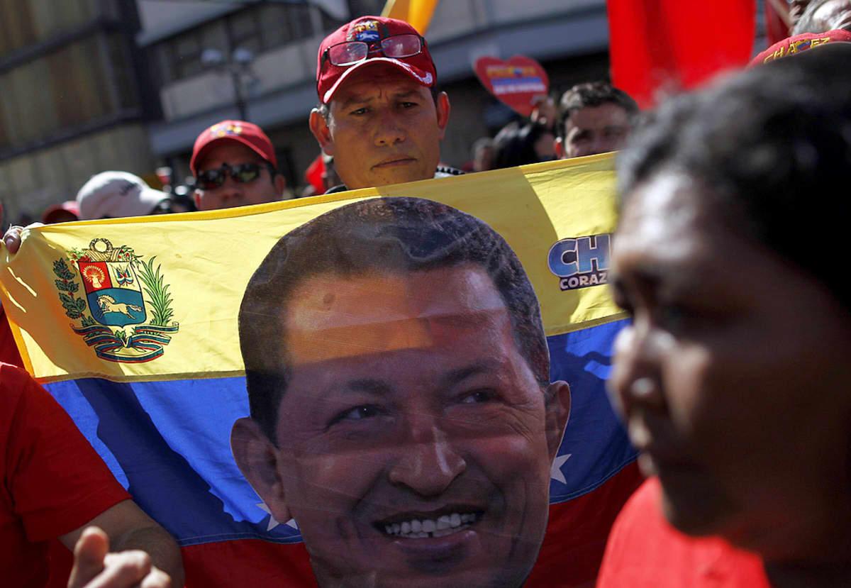 Mies kantaa lippua, jossa on Hugo Chavezin kuva.