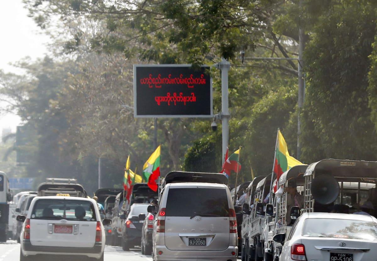 Myanmarin armeijan kannattajat juhlivat heiluttelemalla lippuja autojen ikkunoista.