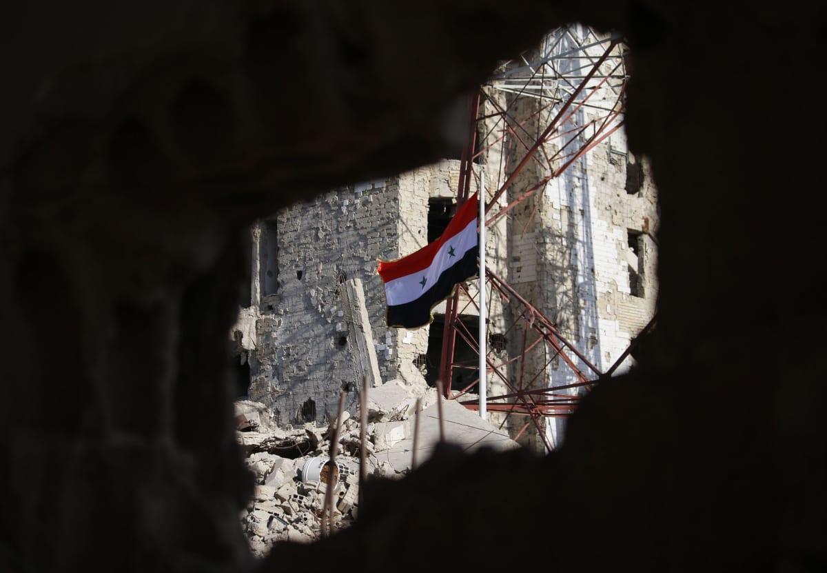 Syyrian lippu liehuu raunioissa.