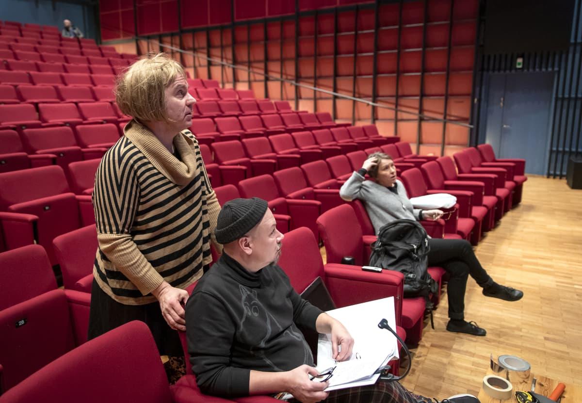 Ohjaaja Antti Lattu, puvustaja Tommi Haapaniemi ja vastaava ohjaaja Hannele Martikainen seuraavat näytelmäharjoituksia.