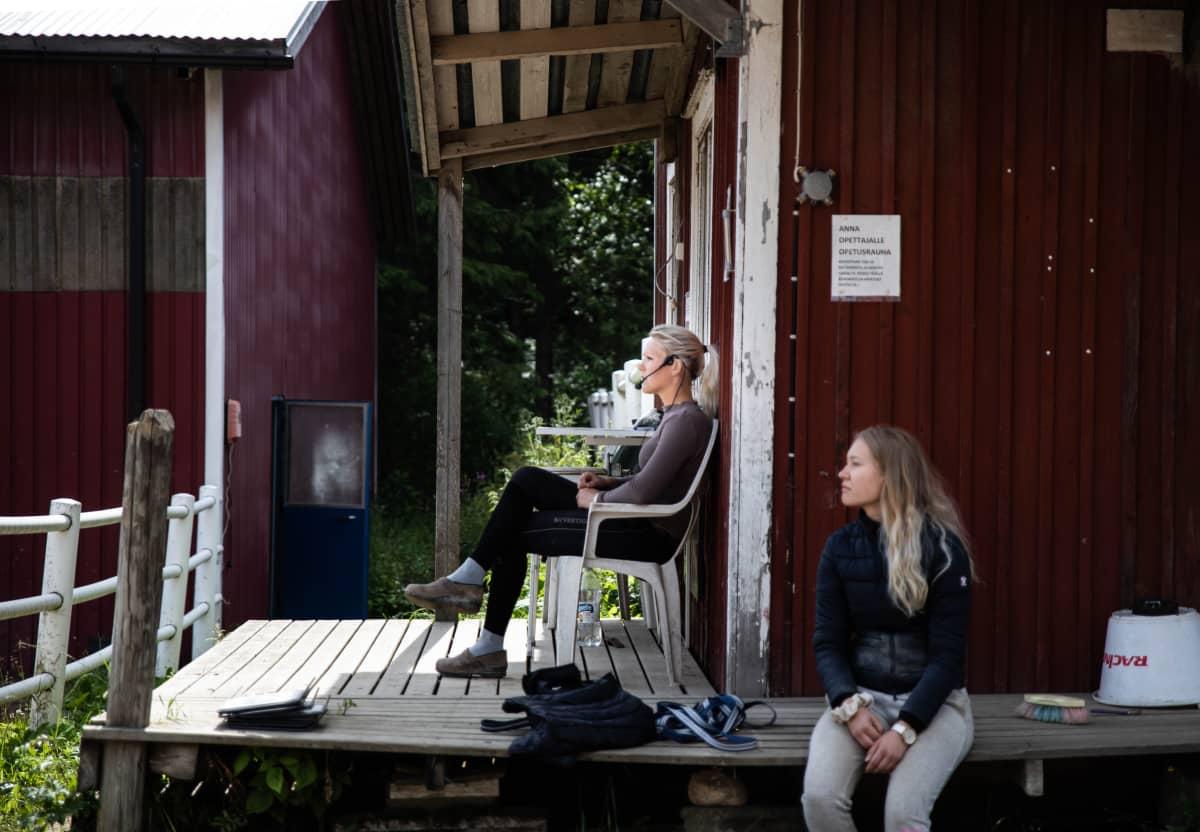 Ratsastuksen opettaja istuu kentän ulkopuolella ja ohjaa tuntia.