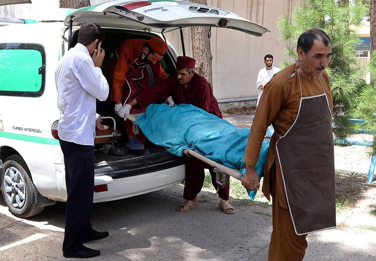 Afganistanilainen lääkintäyksikkö kantaa ammuttuja avustustyöntekijöitä Heratin sairaalan ruumishuoneelle 24. heinäkuuta 2014.