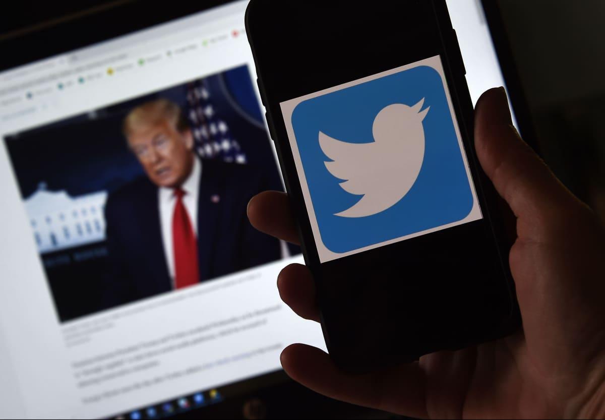 Bild på hand som håller i mobiltelefon med twitterinlägg från Donald Trump.