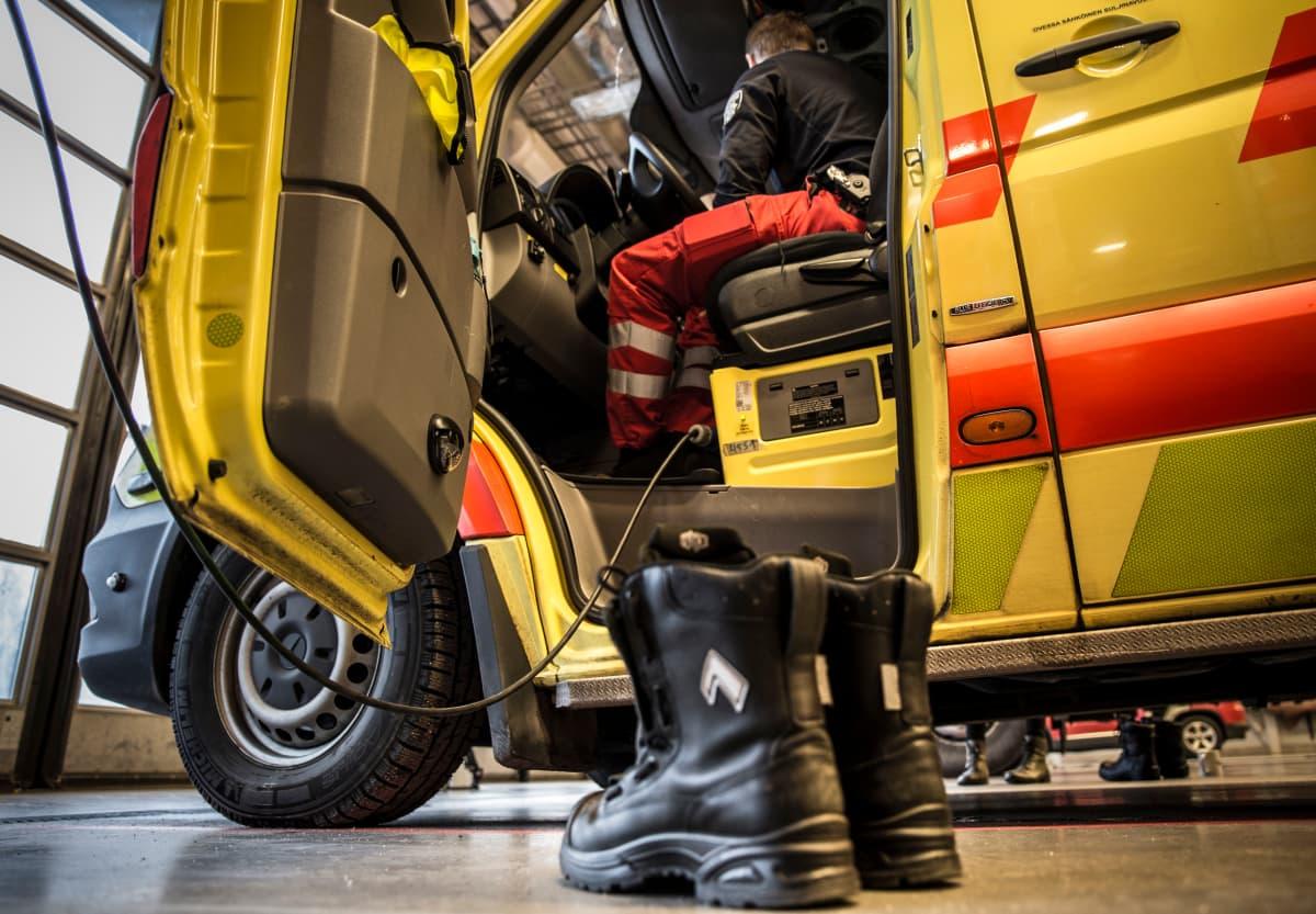 Kengät pelastuslaitoksen lattialla ambulanssin vieressä