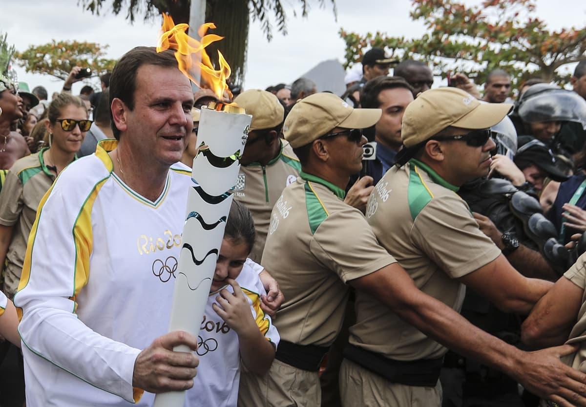 Rio de Janeiron pormestari Eduardo Paes kantaa olympiasoihtua, turvamiehiä