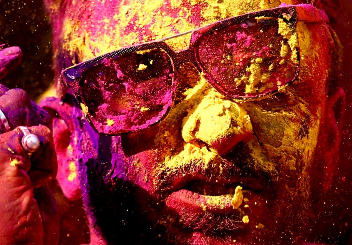 Miehen kasvot ja aurinkolasit ovat värien peitossa.
