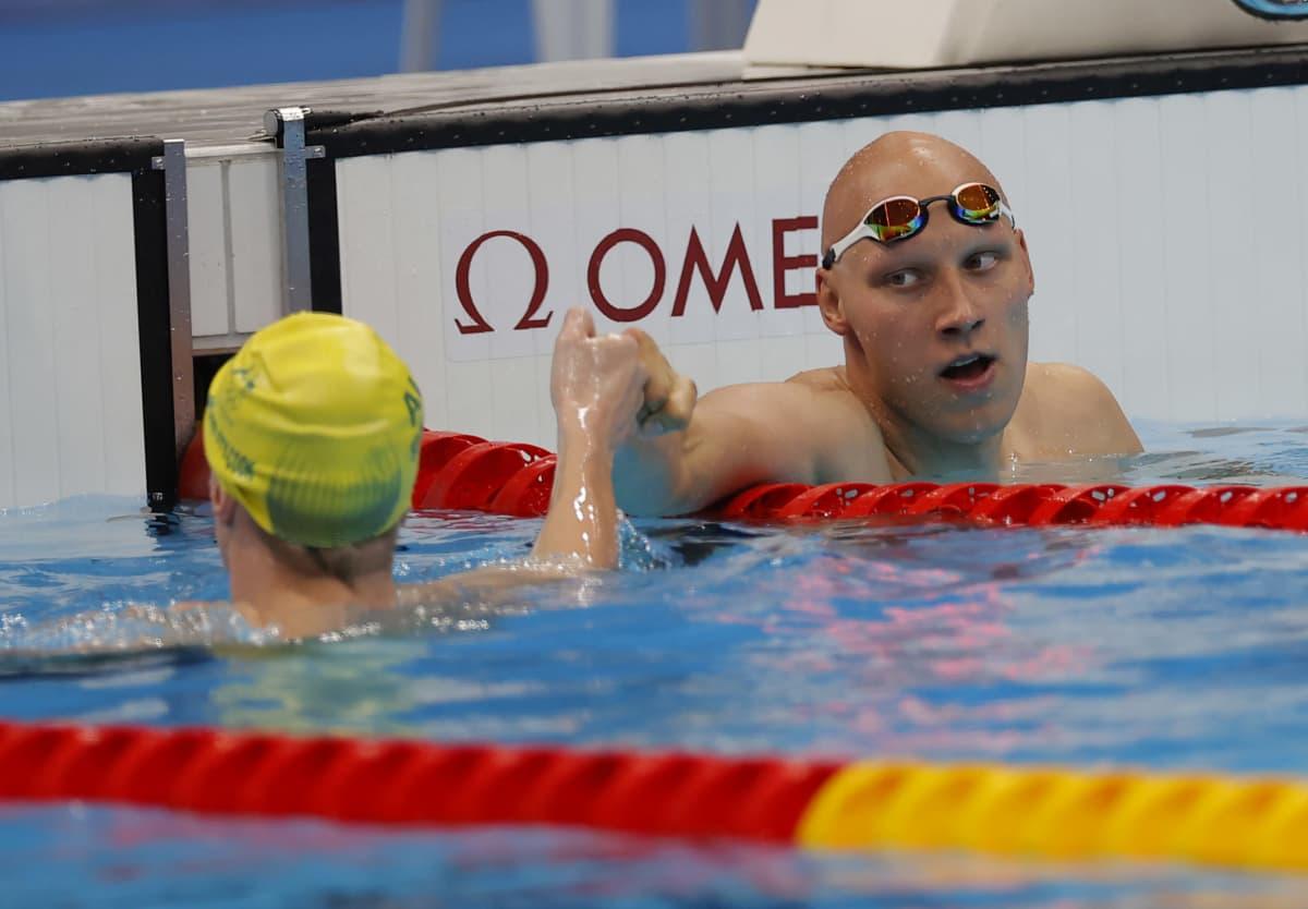 Matti Mattsson iskee nyrkkitervehdyksen viereisen radan uimarin kanssa kisan jälkeen