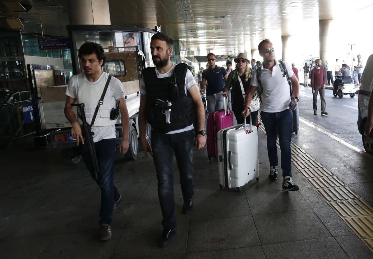 Turisteja laukkujensa kanssa lentokentällä.