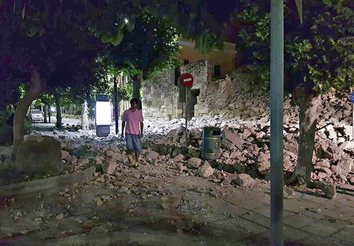 Mies kävelee sortuneen rakennuksen raunioiden ohi Kosin saarella perjantaina aamuyöllä.