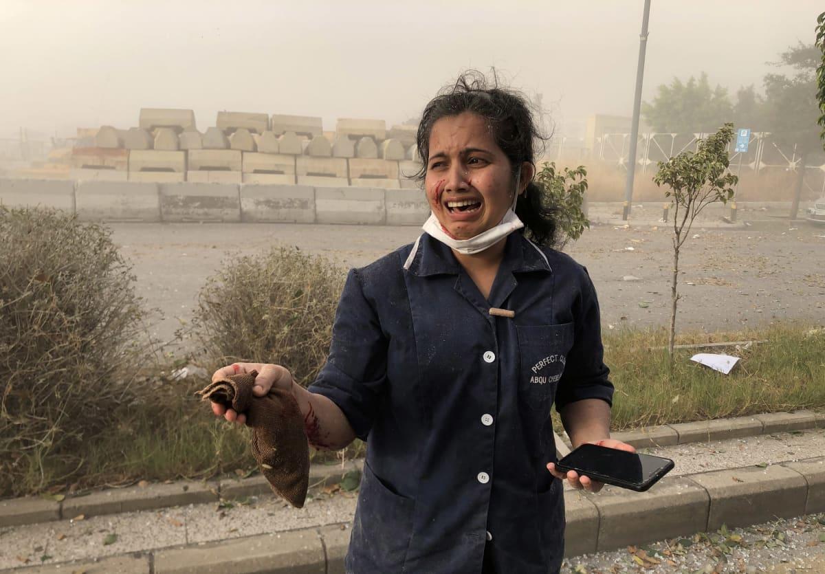 Järkyttynyt nainen Beirutin sataman lähellä tiistaina.