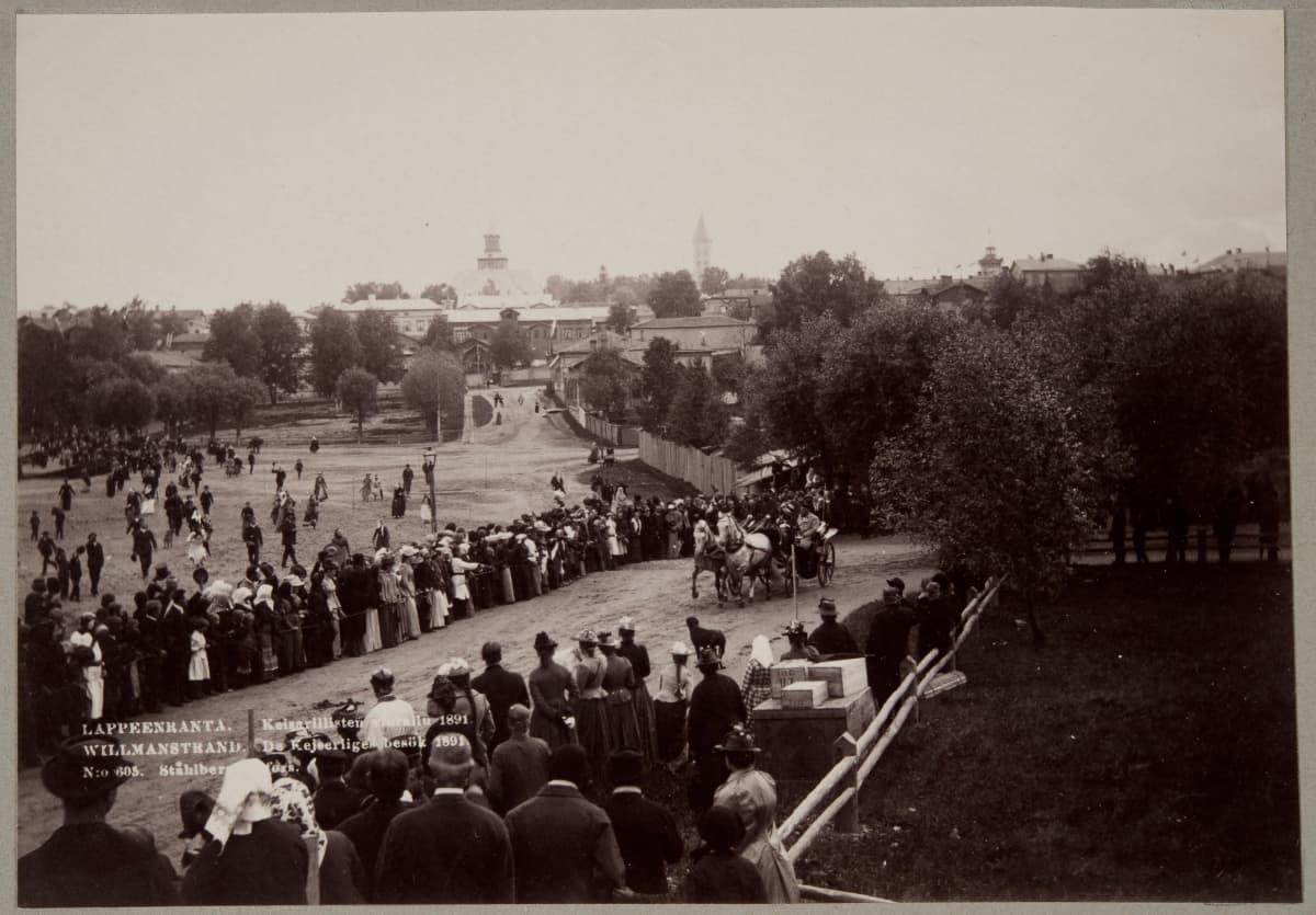 Keisari seurueineen ajaa hevosvankkureissa Lappeenrannan satamaa. Runsaasti yleisöä seuraamassa.