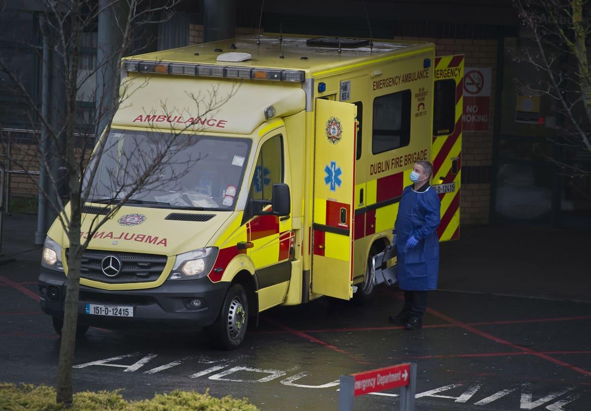 Ambulanssi, jonka vierellä seisoo mies suojavarusteissa.