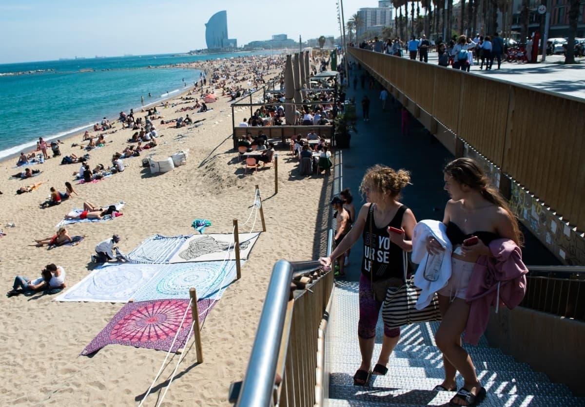 Uimarannalla makailee ja istuskelee ihmisiä. Kaksi nuorta naista nousee portaita rannalta kuvan oikeassa reunassa.