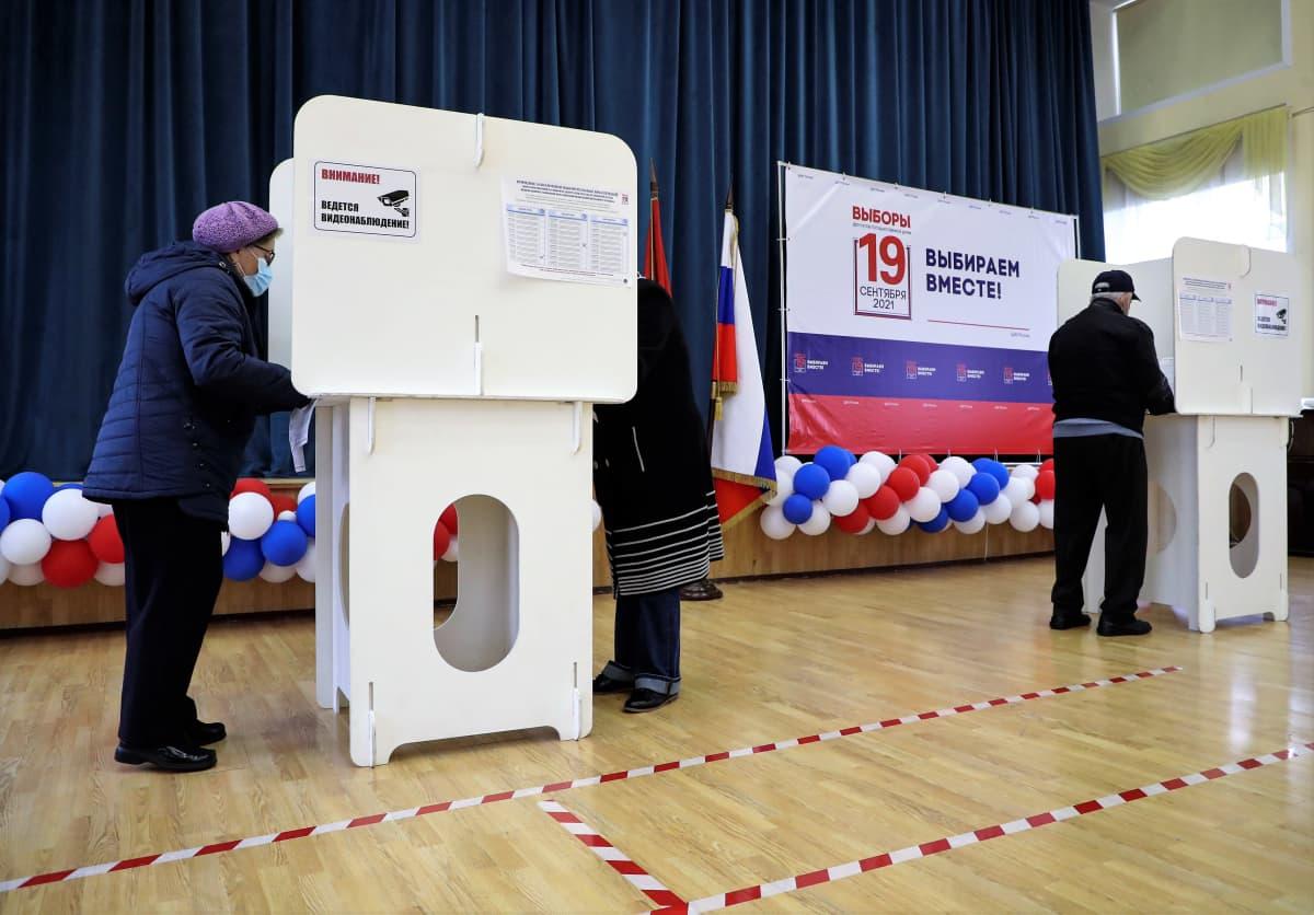 ÄÄnestyspaikalla ihmiset seisovat äänestyskoppien ääressä.