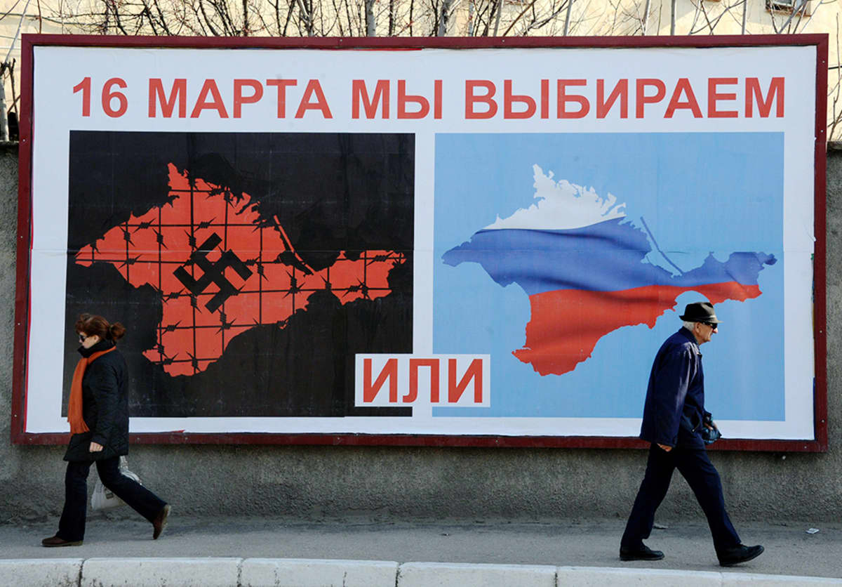 """Ihmisiä kadulla Sevastopolissa 11. maaliskuuta 2014 - mainoksessa lukee: """"16. maaliskuuta valitsemme joko... tai...""""."""