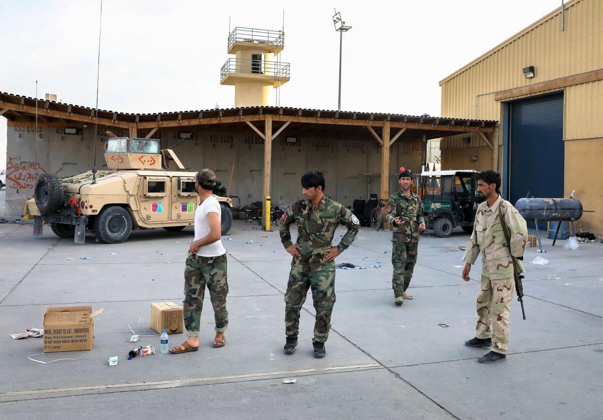 Neljä afgaanisotilasta vaihtelevissa asuissa kävelee ja seisoskelee hylätyn tukikohdan pihalla. Taustalla näkyy lennonjohtotornin näköinen rakennelma. Rakennuksen edessä on panssaroitu ajoneuvo. Maassa on pahvilaatikkoja ja vesipulloja.