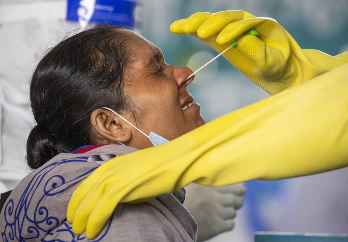 Nainen irvistää, kun hansikoitu käsi työntää koronatestipuikkoa hänen sieraimeensa.