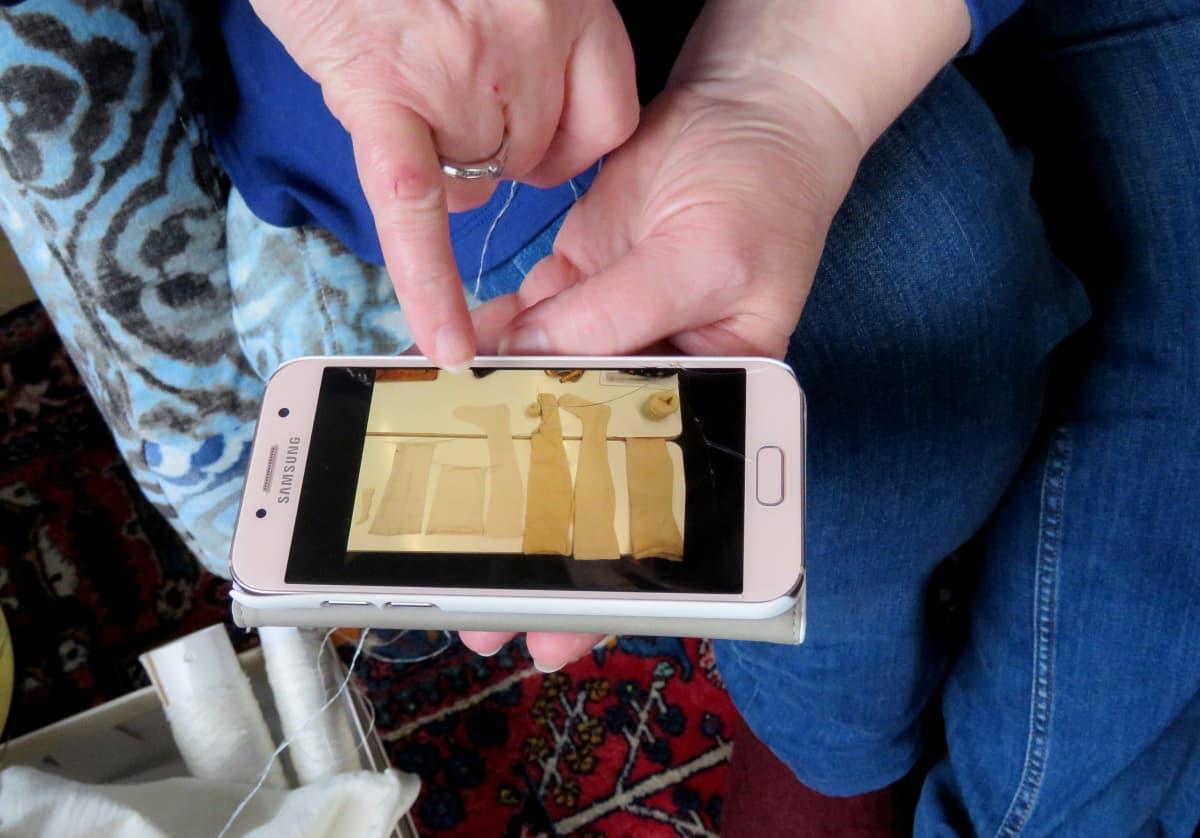 Liisa Kylmänen osoittaa puhelimesta sukkaprojektin valmiiden tuotosten kuvia.