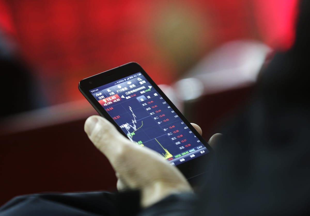 En person håller i en telefon där man kan se aktiekurser.