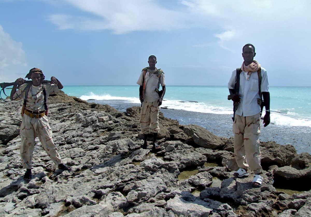 Kolme somalialaista merirosvoa rannikolla. Kaikilla on aseet mukanaan.