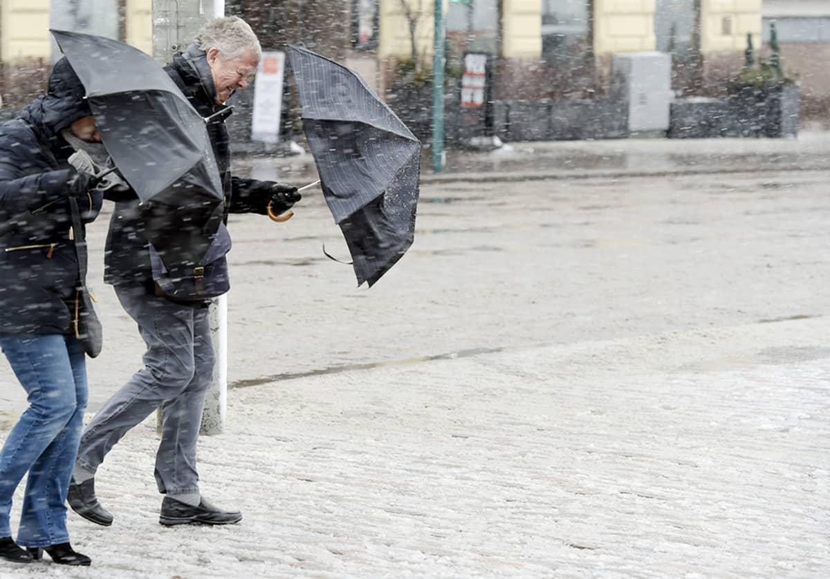 Kuvassa jalankulkijoita lumisateessa Helsingissä 30. maaliskuuta.