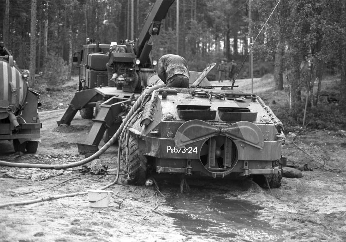 Arkistokuva jossa Saimaaseen uponnut BTR-60 vaunu on nostettu rannalle ja puolustusvoimien henkilökunnan jäsen on tyhjentämässä sitä vedestä pummpausletkulla kesällä 1991