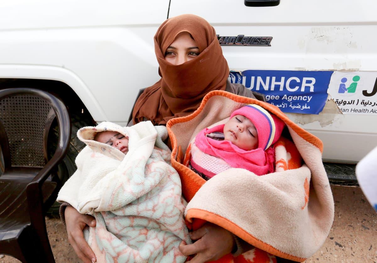 Syyrian pakolainen kahden pienen lapsen kanssa YK:n johtamalla terveusklinikalla.