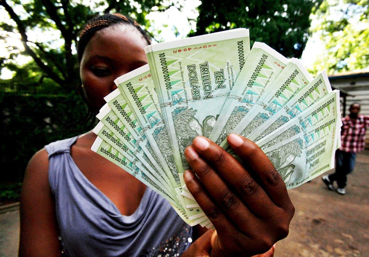 Zimbabwelaisnainen pitelee tukkua kymmenen biljoonan Zimbabwen dollarin seteleitä.