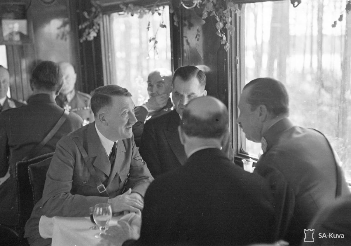 Pöydän ääressä valtakunnankansleri Adolf Hitler, pääministeri Jukka Rangell, tasavallan presidentti Risto Ryti ja marsalkka Mannerheim.