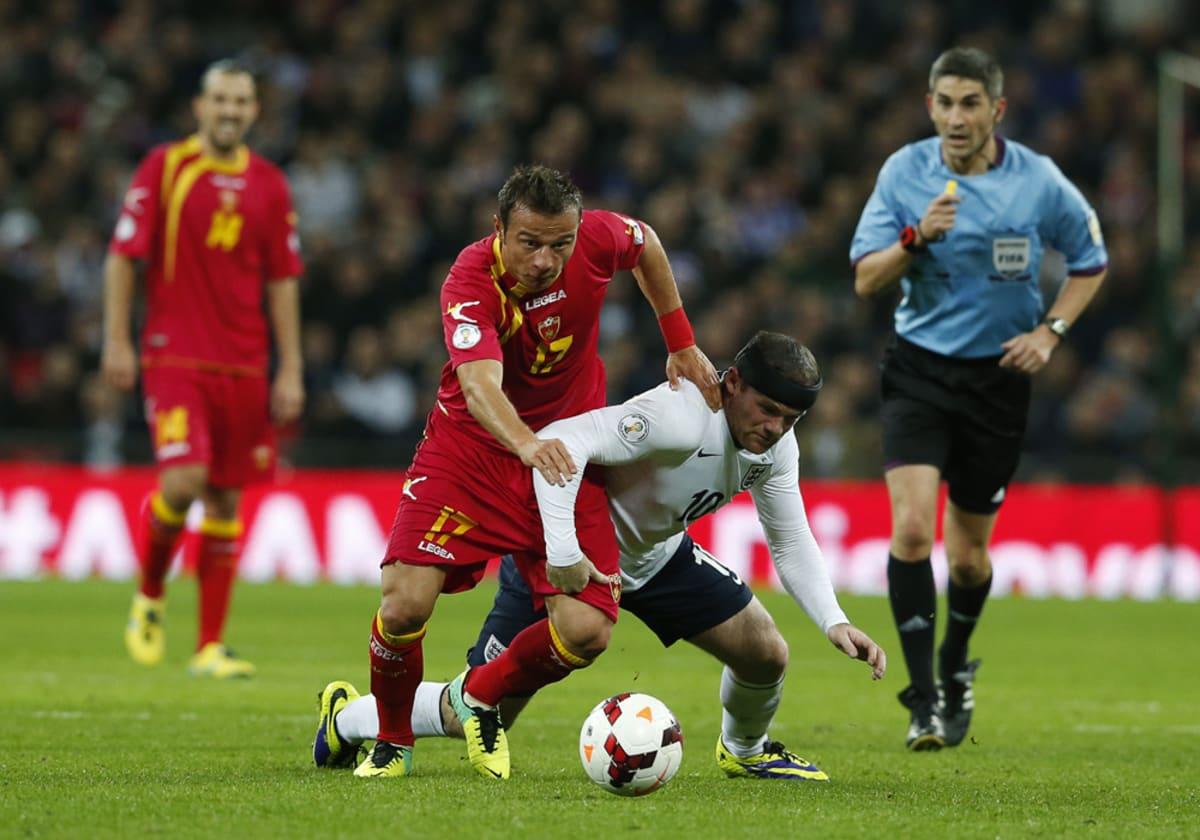 Montenegron Elsad Zverotic (vas.) ja Englannin Wayne Rooney (oik.) kamppailevat pallosta.