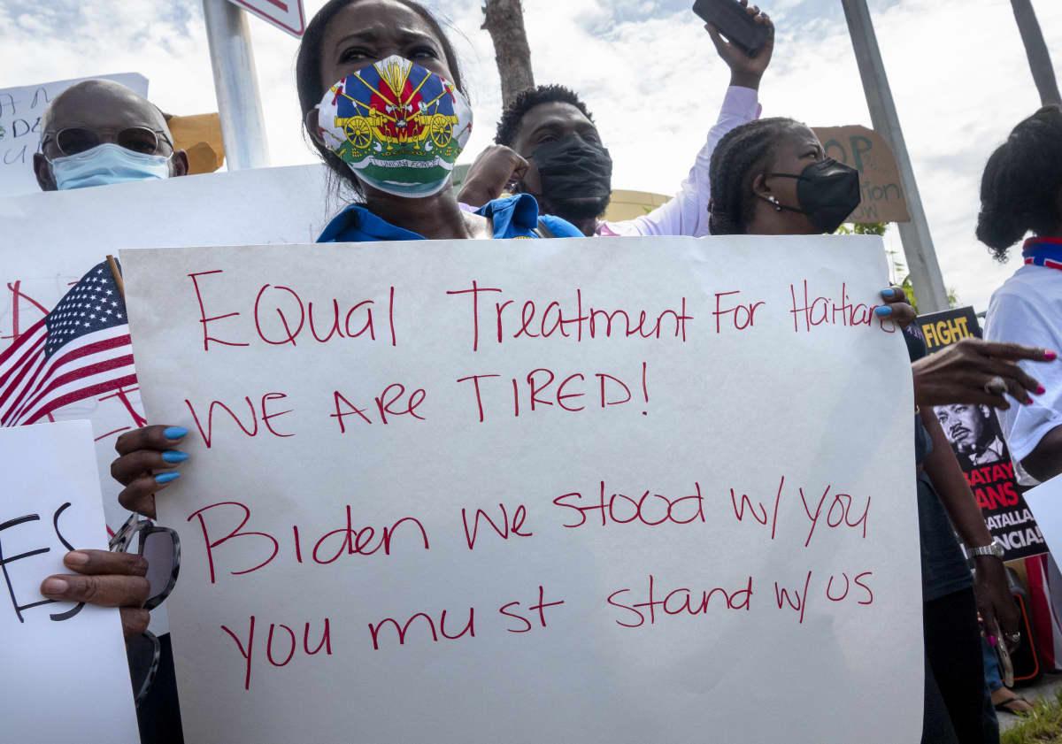 Nainen pitää mielenosoituksessa kylttiä, johon on tussilla kirjoitettu haitilaisten oikeuksia puolustavia lauseita.