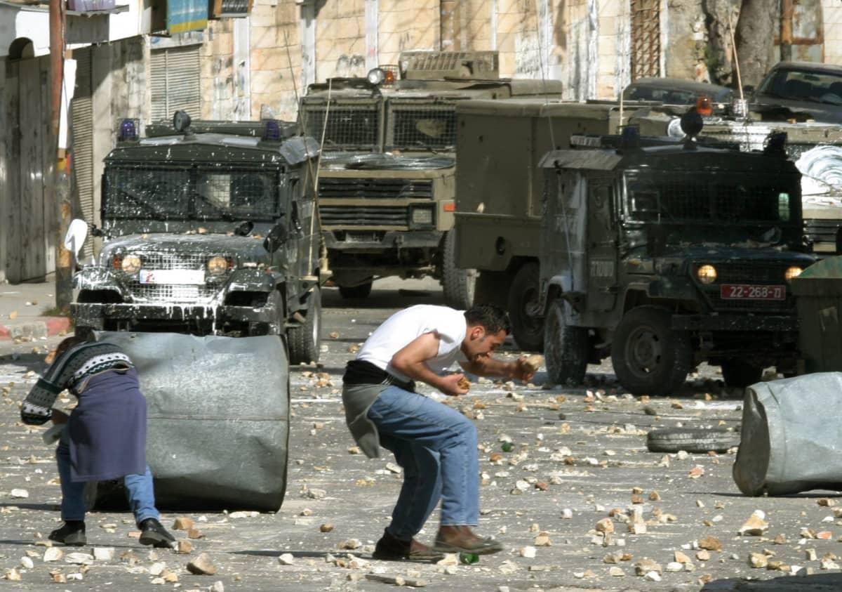 Palestiinalaiset nuoret miehet osoittavat mieltään ja heittivät kiviä israelilaisia ajoneuvoja kohti tammikuussa 2004.