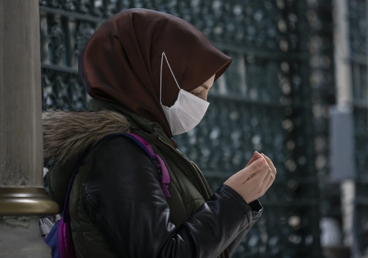 Nainen rukoilee hengityssuojain kasvoillaan moskeijassa Istanbulissa keskiviikkona.