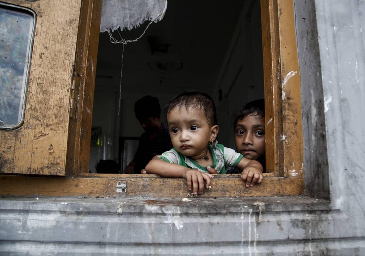 Kaksi vakavailmeistä pikkulasta katselee ikkunasta.