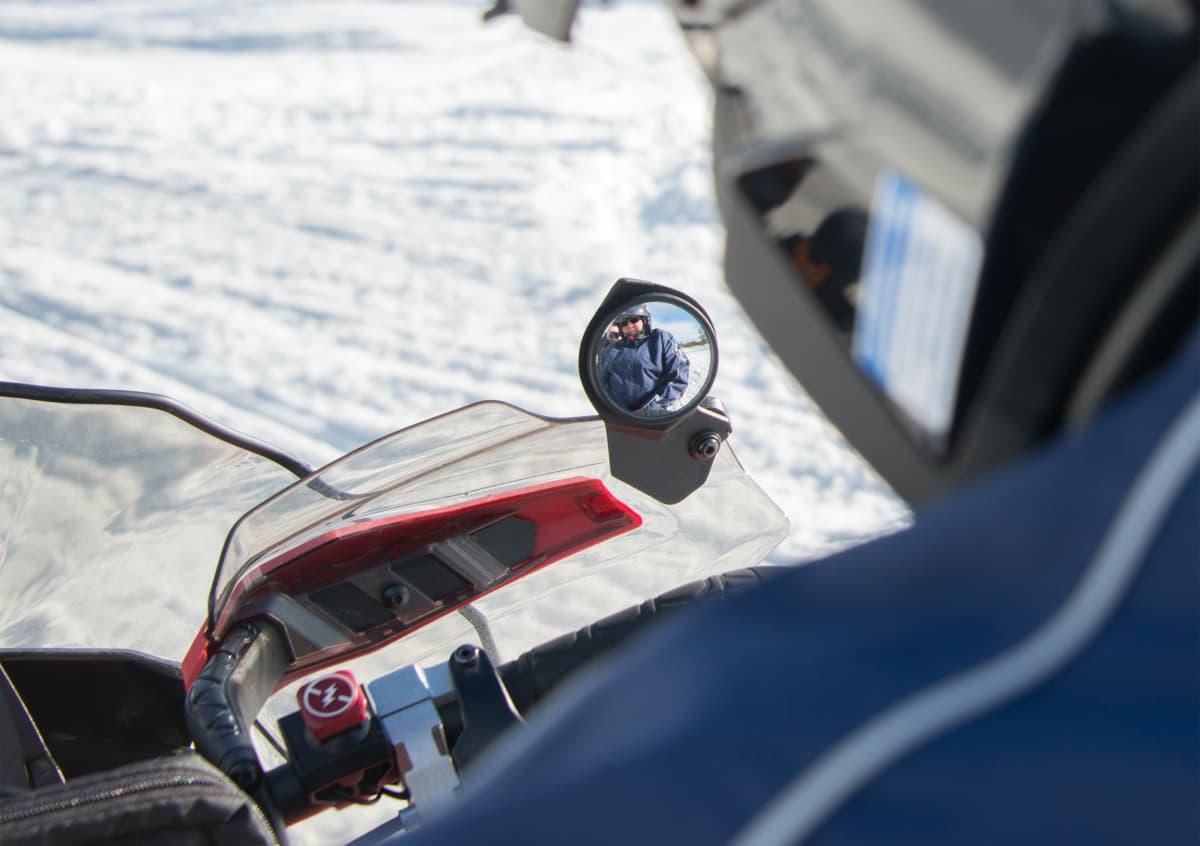 Moottorikelkkailija heijastuu peilistä