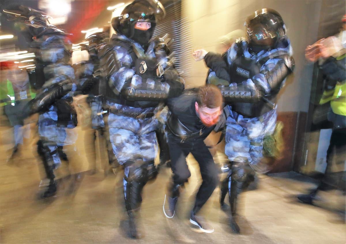 Kaksi mellakkapoliisia kuljettaa välissään nuorta miestä painaen tätä kyyryyn.