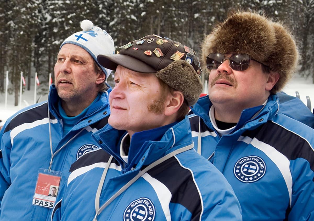 Suomen hiihtomaajoukkueen asuissa olevat miehet katsovat intensiivisesti urheilusuoritusta.