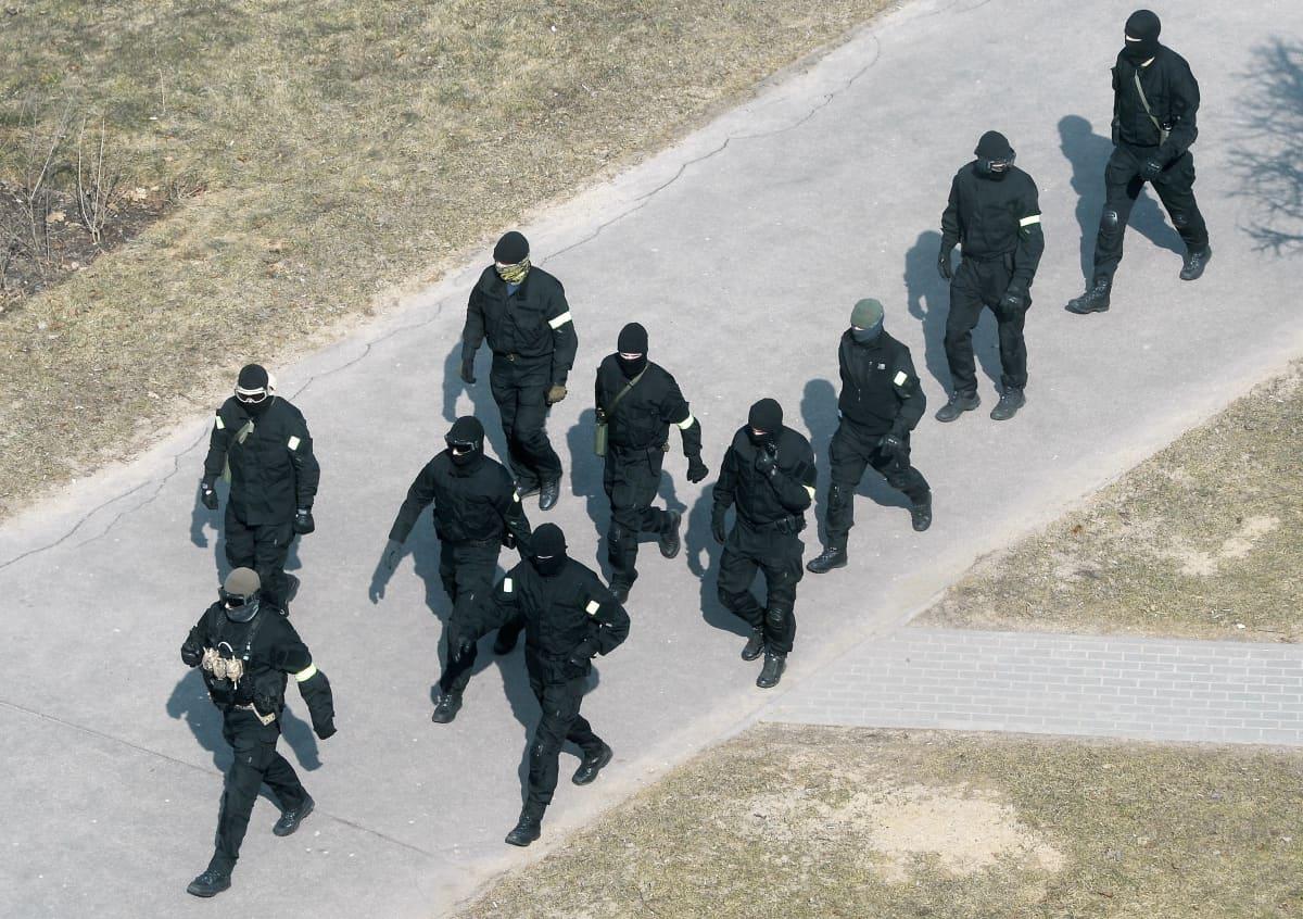 Joukko mustiin asuihin pukeutuneita poliiseja marssii kadulla.