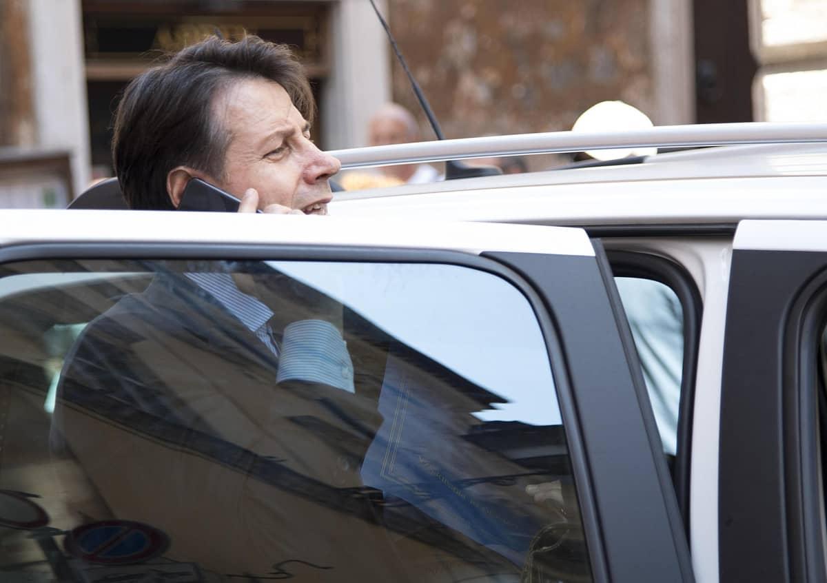 Kuvassa Giuseppe Conte on auton auki olevan oven takana puhumassa kännykkään.